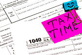 Tax time written on a bright sticker note paper clip for a tax form