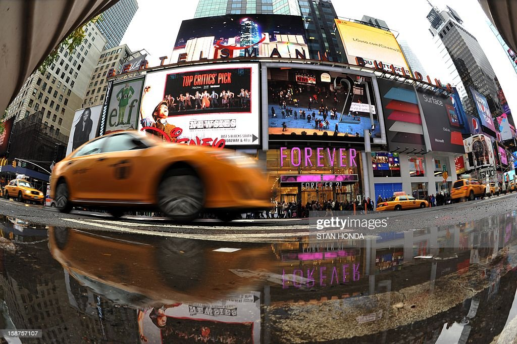 Taxi and building are reflected in a puddle December 27, 2012 in New York's Times Square. AFP PHOTO/Stan HONDA