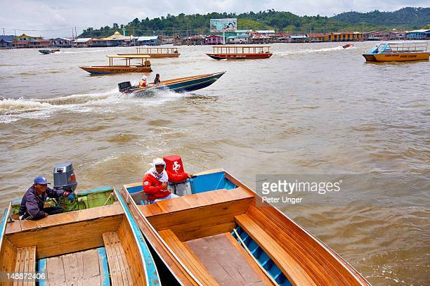 Taxi boat divers waiting on Sungai Brunei river for trips to Kampong Ayer floating village.