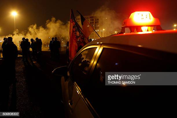 A taxi car stand in front of police forces during a demonstration on January 26 2016 early in the morning at porte Maillot in Paris AFP PHOTO /...