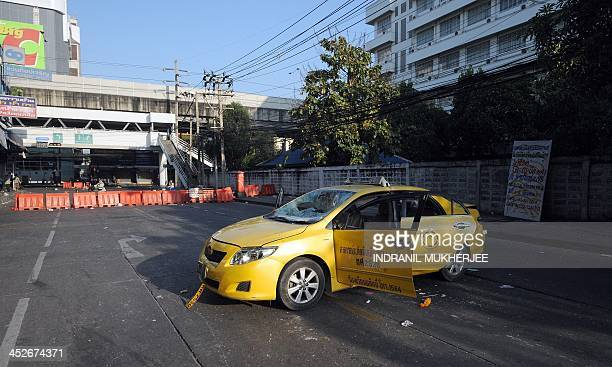 A taxi damaged during clashes between antigovernment protestors and progovernment Red Shirt supporters is seen on a road in Bangkok on December 1...