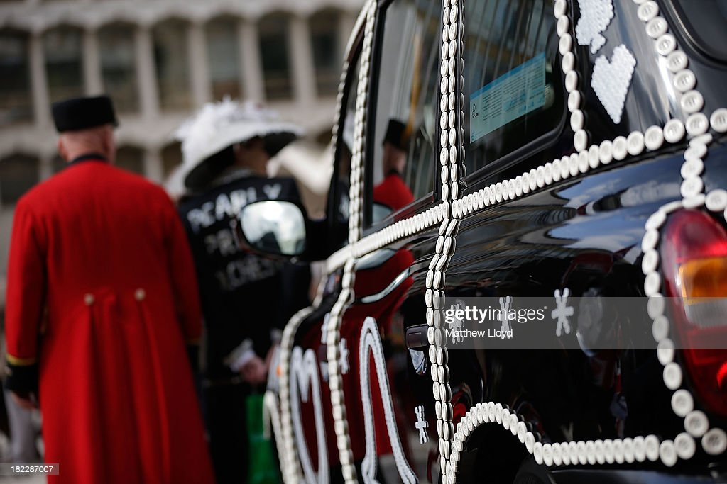 A taxi decorated in Pearly regalia in the Guildhall Yard on September 29, 2013 in London, England. The Harvest Festival features dancing and entertainment by participants in traditional costumes and concludes with a service at St Mary-le-Bow Church, home of the renowned Bow Bells. Dressing as a Pearly King or Queen, by wearing clothes adorned with pearl buttons, originated in the 19th century when London street sweeper Henry Croft decorated his uniform and began collecting money for charity