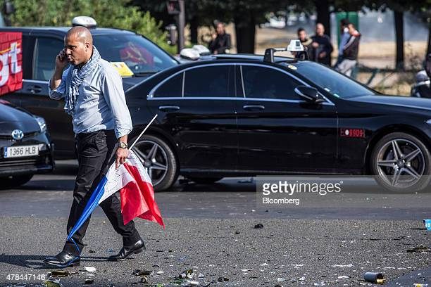 A taxi diver speaks on a mobile phone as he carries a French national flag while cab drivers protest against Uber Technologies Inc's car sharing...
