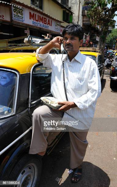Taxi driver and old mobile phone in Mumbai on March 15 2014 in Mumbai India