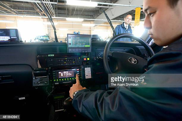 A taxi driver changes the setting of the meter before the eight percent consumption tax is applied on April 1 on March 31 2014 in Tokyo Japan Japan...