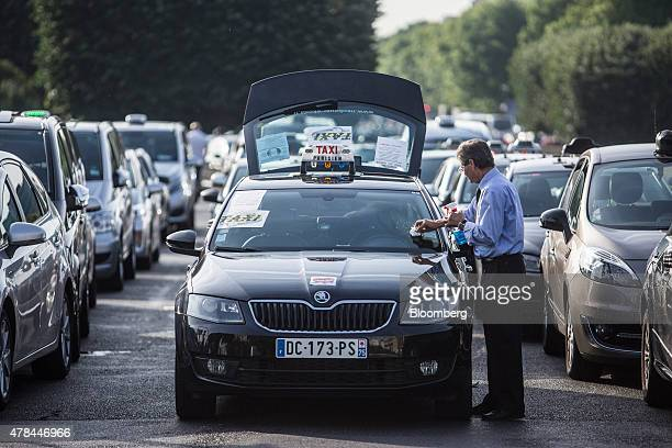 A taxi driver cleans his windscreen as French cab drivers sit parked during a protest against Uber Technologies Inc's car sharing service in Paris...