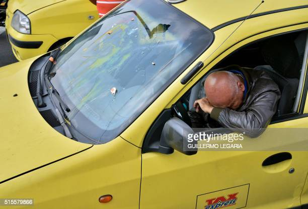 A taxi driver complains after having been attacked by other taxi drivers because he does not participate in a protest in Bogota on March 14 against...