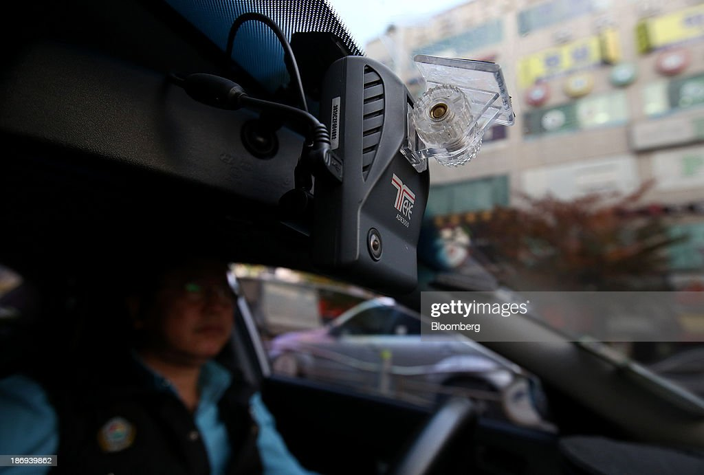 A taxi driver drives as a Joutec Teye black box camera operates inside his vehicle in Incheon, South Korea, on Monday, Nov. 4, 2013. Black boxes for cars are devices that automatically record video and audio as well as time, location and speed. Photographer: SeongJoon Cho/Bloomberg via Getty Images