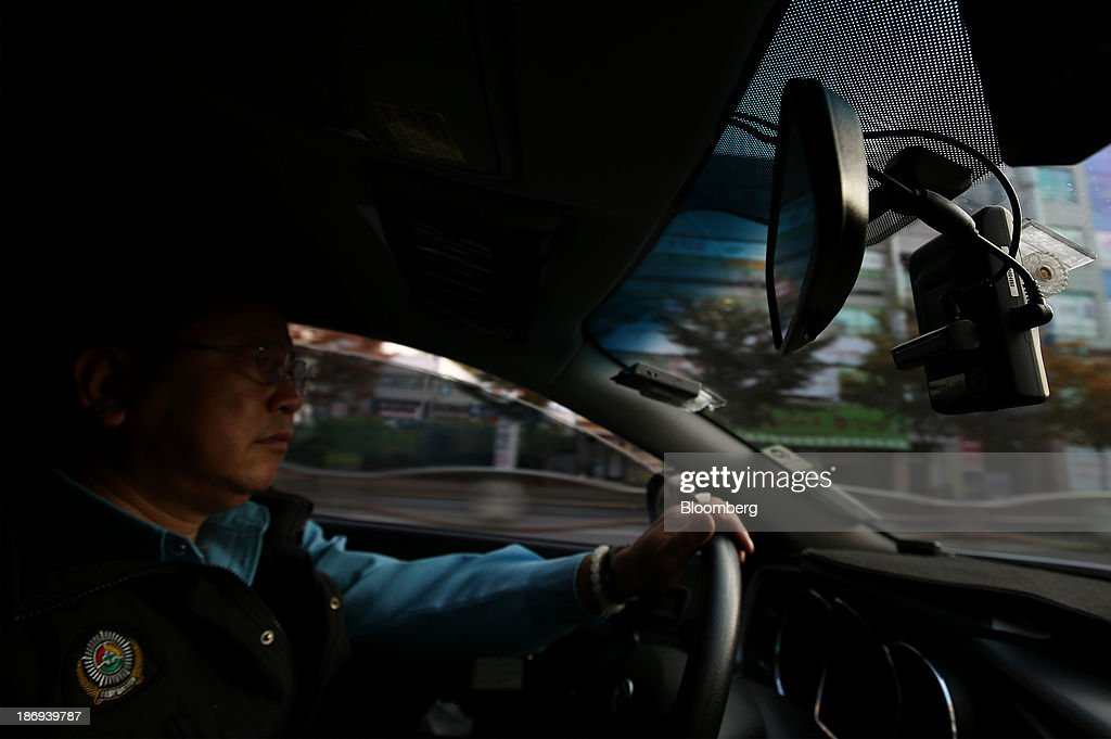 A taxi driver drives as a Joutec Teye black box camera, right, operates inside his vehicle in Incheon, South Korea, on Monday, Nov. 4, 2013. Black boxes for cars are devices that automatically record video and audio as well as time, location and speed. Photographer: SeongJoon Cho/Bloomberg via Getty Images