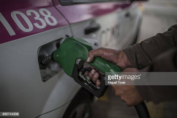 A taxi driver fills up his car's trunk at a gas station in Copilco avenue on December 31 2016 in Mexico City Mexico Officials say it's time for...