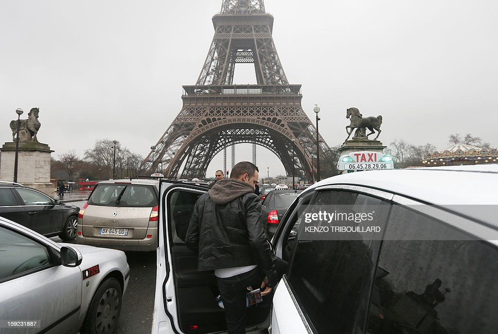 A taxi driver gets into his car in front of the Eiffel tower on January 10, 2013 during a nationwide demonstration in Paris to protest against legislative changes concerning the transport of sick and incapacitated passengers.