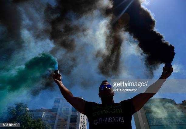 A taxi driver holds a smoke canister during a demoonstation against the competition from rival transport companies Uber and Cabify in the centre of...