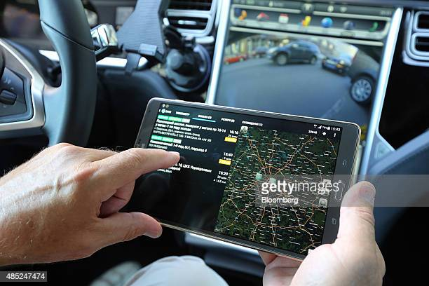 A taxi driver in a Tesla Motors Inc Model S 85 electric automobile operated by the YandexTaxi online service uses a smartphone app to accept a...