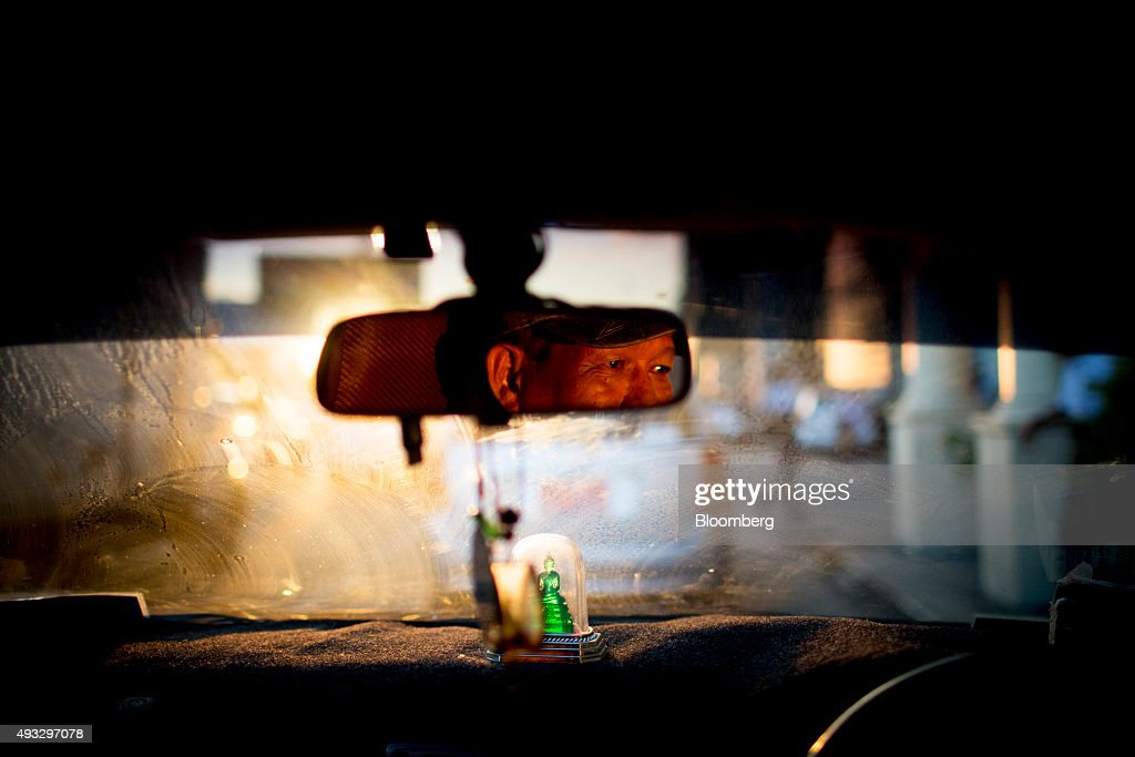 A taxi driver is reflected in a car's rearview mirror in Yangon, Myanmar, on Thursday, Oct. 15, 2015. Myanmar's government signed a cease-fire agreement with half of the nation's armed ethnic groups, a partial victory for President Thein Sein less than a month before an historic national election. Photographer: Brent Lewin/Bloomberg via Getty Images