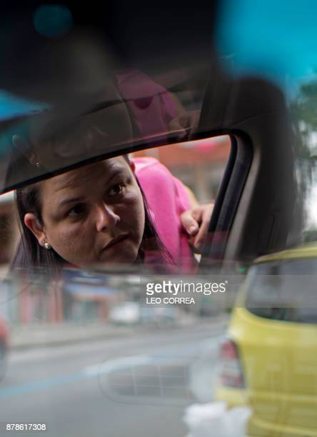 Taxi driver Luciana Mazzei stands at the door of her car as she poses for the picture in Rio de Janeiro Brazil on November 24 2017 Mazzei is one of...