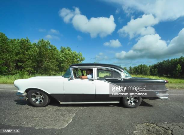 Taxi driver on a black and white vintage car avoiding potholes on Cuba'a national highway