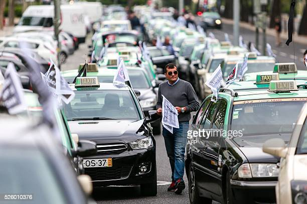 A taxi driver prepares to take part in a slow convoy in Lisbon on April 29 2016 protesting against US cab giant Uber which they accuse of illegally...