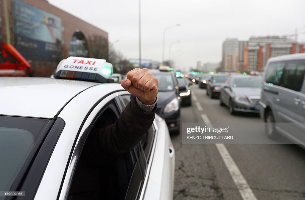 A taxi driver raises his fist while taking part in a nationwide demonstration on a highway near Paris on January 10, 2013 to protest against legislative changes concerning the transport of sick and incapacitated passengers.