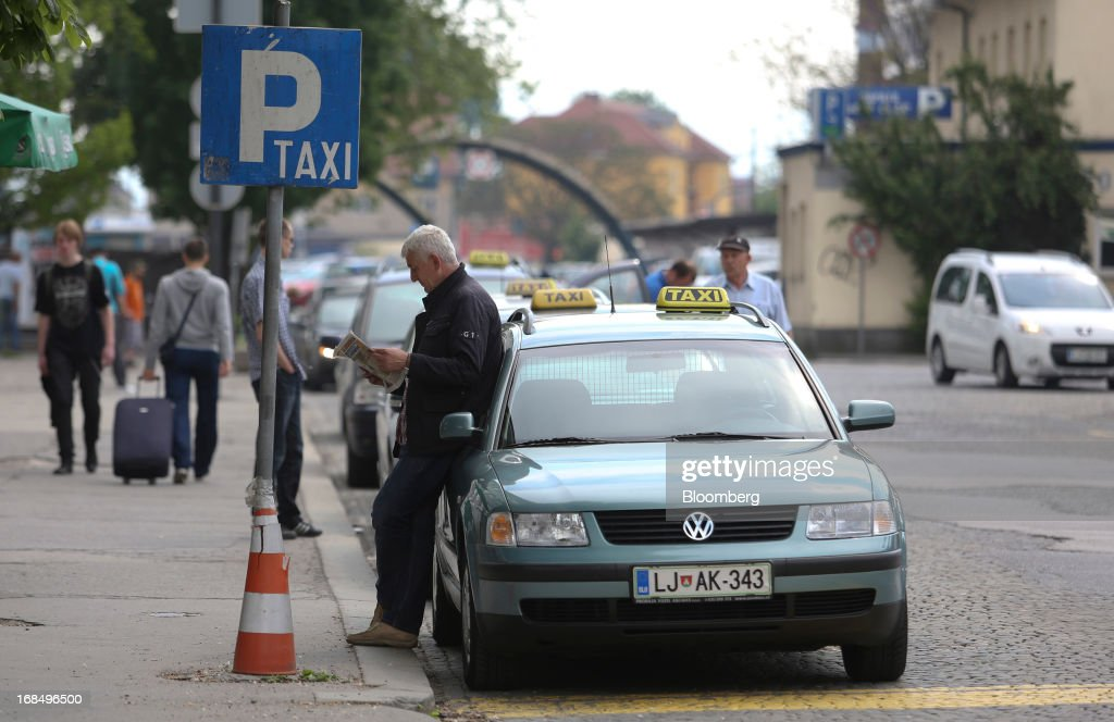 A taxi driver reads a newspaper while waiting for customers at a taxi rank in Ljubljana, Slovenia, on Friday, May 10, 2013. The Adriatic nation is seeking to fix its ailing lenders with a cash injection of at least 900 million euros ($1.17 billion) after Cyprus's bailout focused investors on countries with weak banking industries. Photographer: Chris Ratcliffe/Bloomberg via Getty Images