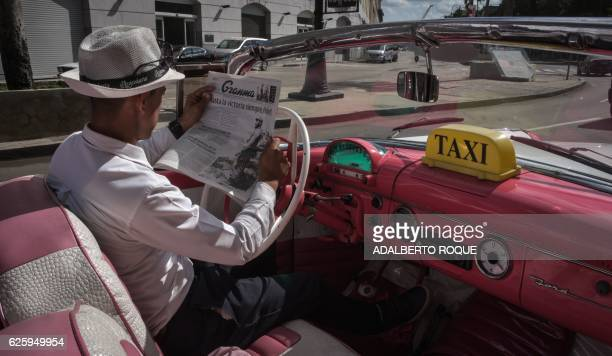 TOPSHOT A taxi driver reads the newspaper in a street of Havana on November 26 the day after Cuban revolutionary leader Fidel Castro died aged 90 One...