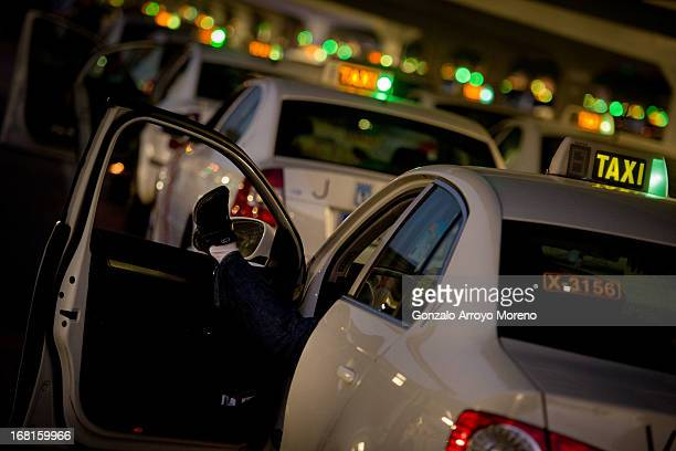 A taxi driver rests in his car at the T4 terminal taxi rank at MadridBarajas airporton April 23 2013 in Madrid Spain According to taxi association...