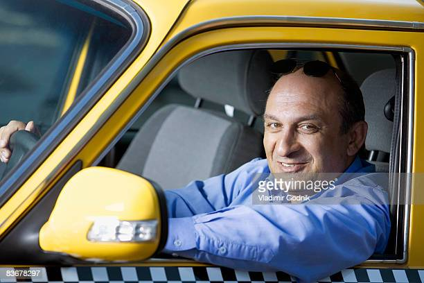 A taxi driver sitting in his car