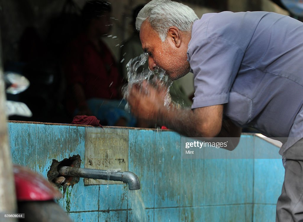 A taxi driver splashing water on the face in Babughat Bus stand area on a hot summer day on May 28, 2015 in Kolkata, India.