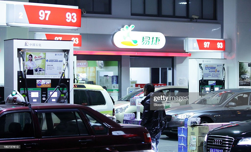 A taxi driver stands near vehicles refueling at a China Petroleum & Chemical Corp. (Sinopec) gas station in Shanghai, China, on Wednesday, Jan. 30, 2013. Sinopec, Asia's biggest refiner, will raise HK$24 billion ($3.1 billion) in its biggest share sale since listing in 2000 as it looks to add production assets. Photographer: Tomohiro Ohsumi/Bloomberg via Getty Images