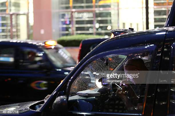 A taxi driver uses his smartphone as he sits inside his black London cab whilst waiting for customers outside office buildings in the Canary Wharf...