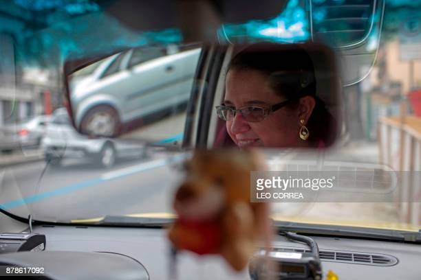 Taxi driver Vanessa Moura poses for the picture inside her cab in Rio de Janeiro Brazil on November 24 2017 Moura who has been working for two years...