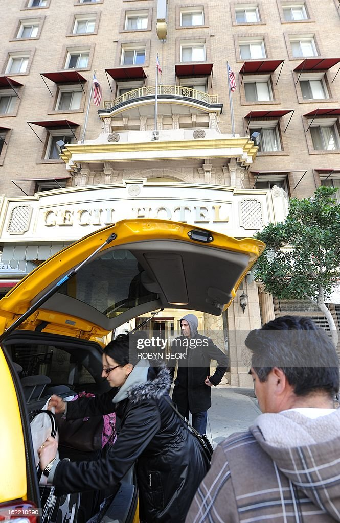 A taxi driver (R) waits as married British tourists Mike and Sabina Baugh, both 27, put their bags in a taxi as they leave the Cecil Hotel to relocate to a different hotel, in Los Angeles California February 20, 2013. The body of 21-year-old Canadian tourist Elisa Lam was found in a water tank on the roof of the hotel three weeks after she went missing, police said. The corpse was found February 19 after hotel guests complained of low water pressure. AFP PHOTO/Robyn BECK