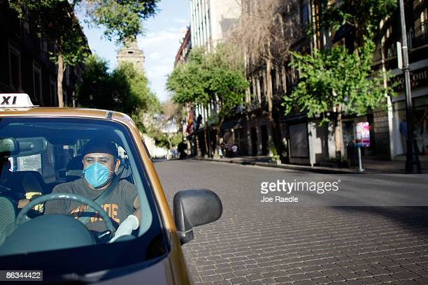 A taxi driver waits at a traffic light in a normally busy street but because of the beginning of a national holiday and the government advising...