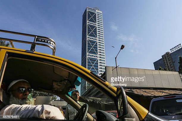 A taxi driver waits for customers in front of the Sunshine Tower developed by Sunshine Housing Infrastructure Ltd in the Dadar area of Mumbai India...
