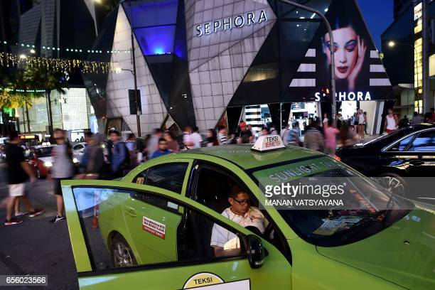 A taxi driver waits for customers in the busy Bukit Bintang tourist spot of Kuala Lumpur on March 21 2017 / AFP PHOTO / Manan VATSYAYANA