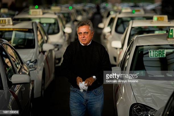 A taxi driver walks on after cleaning his taxi glasses in the middle of the Atocha railway station taxi rank on April 26 2013 in Madrid Spain...