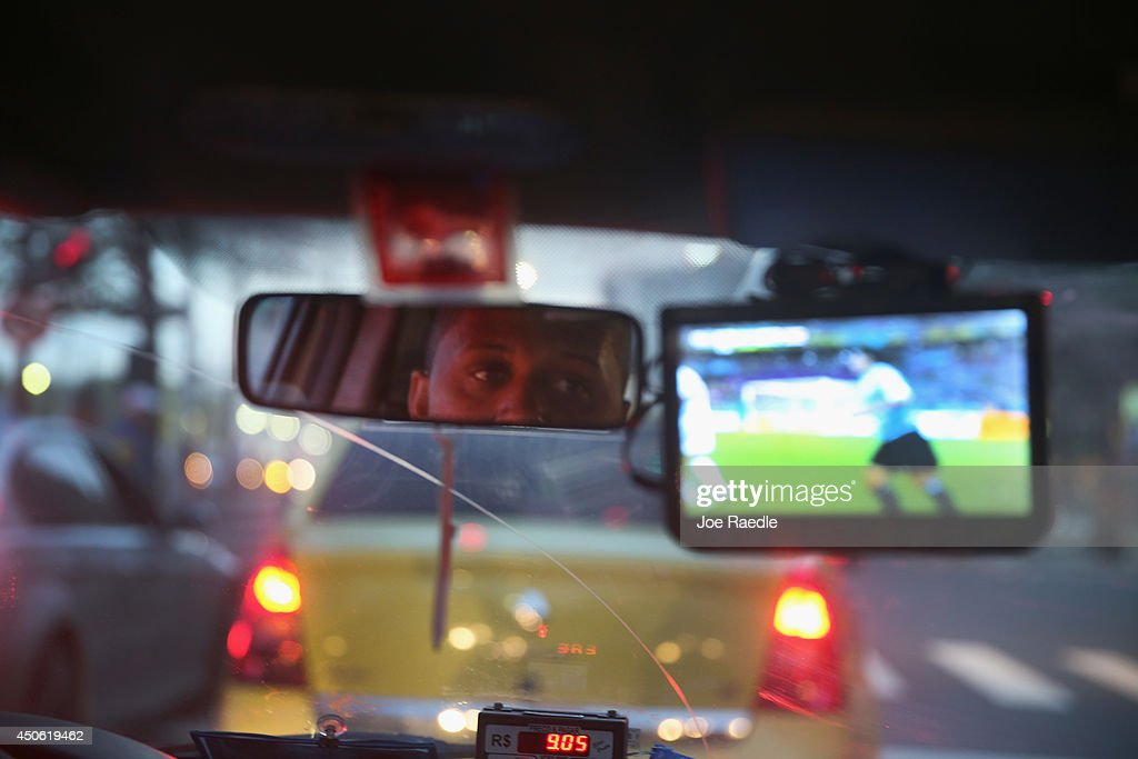A taxi driver watches Uruguay and Costa Rica play on his small television set as the FIFA World Cup continues on June 14, 2014 in Rio de Janeiro, Brazil. The match was played on the third day of the World Cup tournament.