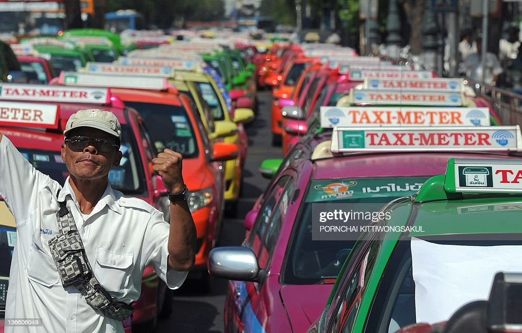 Taxi drivers a protest against the hike of natural gas for vehicles (NGV) price in front of the Government House in Bangkok on January 9, 2012. Thai transport entrepreneurs protested at two locations in the capital against the cabinet resolution to raise the price of natural gas for vehicles (NGV) by 6 bahts per kilograms within a year.