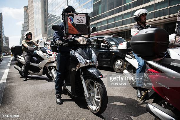 Taxi drivers and scooter riders currently training for their license take part in a demonstration in central London on May 26 against mobile app Uber...