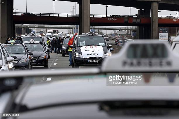 Taxi drivers block a road with their taxis on February 10 2014 near the Roissy Charles de Gaulle airport outside Paris to protest against competition...