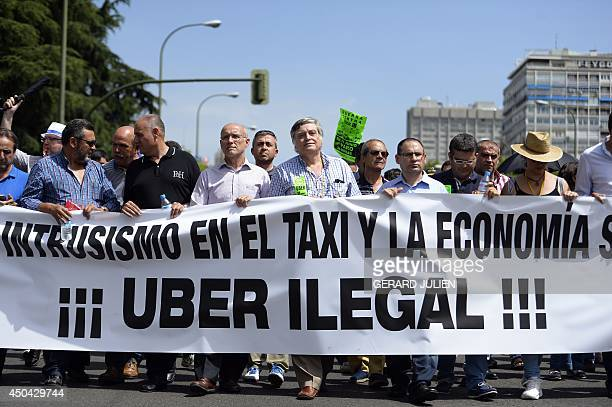 Taxi drivers carry a banner during a strike action in protest of unliscensed taxitypeservices in central Madrid on June 11 2014 Taxi drivers in...