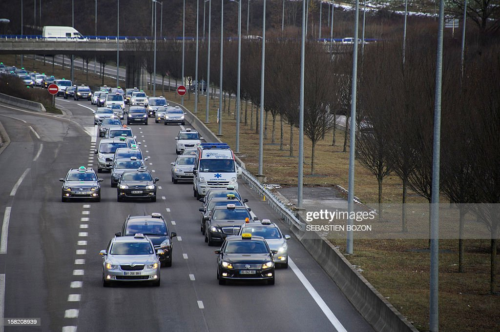 Taxi drivers drive during a 'go slow' strike action on a road in Besancon on December 11, 2012 protesting a proposed law that would allow a tender process to take place for the transport of medical patient between their home and hospitals. Some 200 taxis took part in the action. AFP PHOTO / SEBASTIEN BOZON