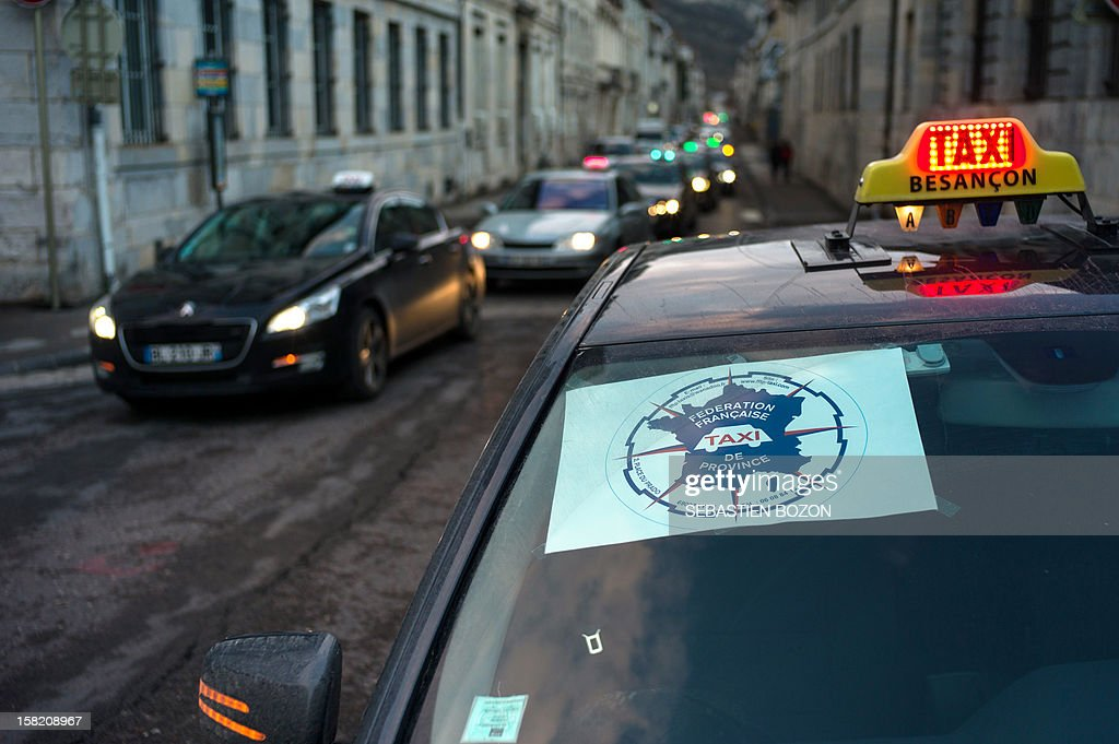 Taxi drivers drive during a 'go slow' strike action on a road in Besancon on December 11, 2012 protesting a proposed law that would allow a tender process to take place for the transport of medical patient between their home and hospitals. Some 200 taxis took part in the action.