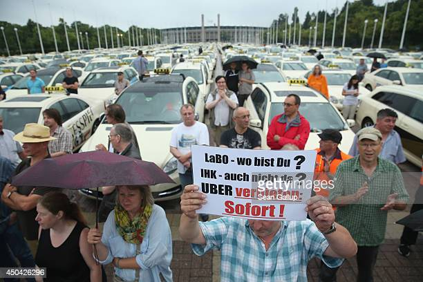 Taxi drivers including one demanding the prohibition of the Uber app service gather next to the Olympia Stadium to protest ridesharing apps on June...