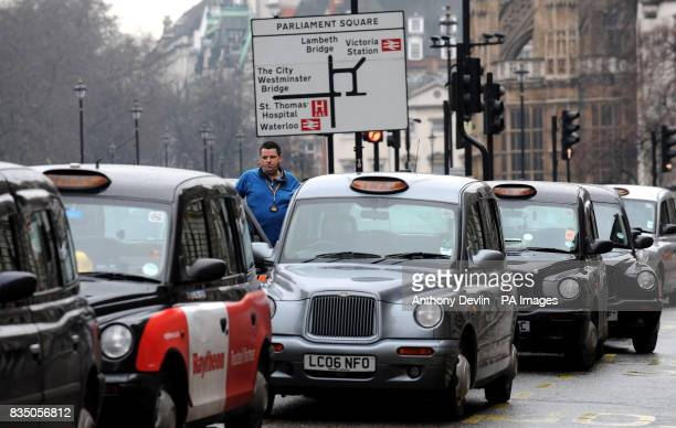 Taxi drivers line the street in Whitehall London in protest over a rank for private vehicles