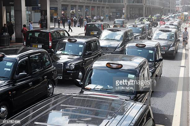 Taxi drivers take part in a 'go slow' demonstration in central London on May 26 against mobile app Uber and regulator Transport for London to...