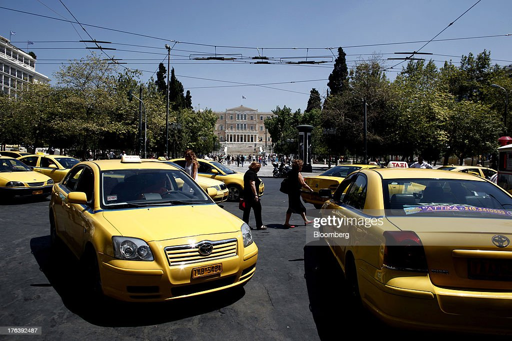 Taxi drivers wait for customers in their yellow cabs parked near the Greek national parliament, center, in Syntagma square in Athens, Greece, on Friday, Aug. 9, 2013. Greece's economy contracted for a 20th quarter, extending an economic slump that has left more than six in 10 young Greeks out of work. Photographer: Angelos Tzortzinis/Bloomberg via Getty Images