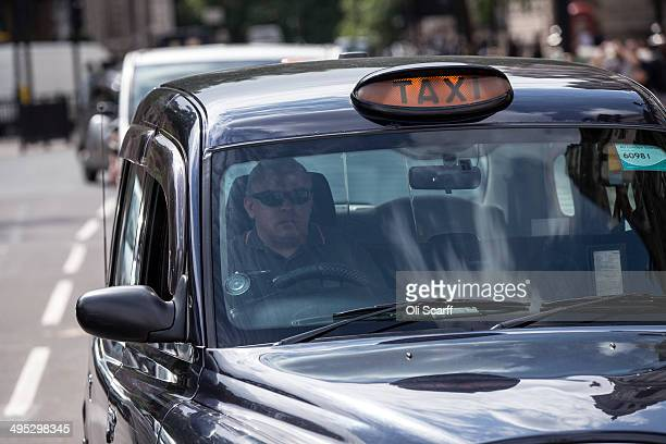 A taxi drives on the streets of Westminster on June 2 2014 in London England The controversial mobile application 'Uber' which allows users to hail...