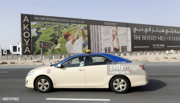 A taxi drives past a billboard showing US realestate magnate Donald Trump playing golf advertising the Trump International Golf Club Dubai in the...