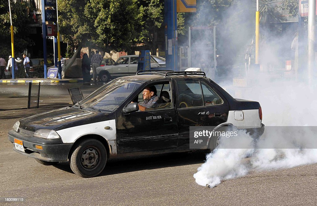 A taxi drives past a tear gas canister thrown by Egyptian security forces during clashes between supporters and opponents of the ousted Egyptian president in the capital Cairo on October 4, 2013. Clashes erupted between supporters and opponents of ousted president Mohamed Morsi in two districts of Cairo after Friday prayers as thousands of Islamists held fresh anti-military protests, witnesses and an AFP reporter said.