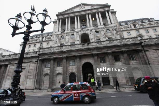 A taxi drives past the front of the Bank of England in London's financial district after it was announced that UK economy shrank by 02% during the...